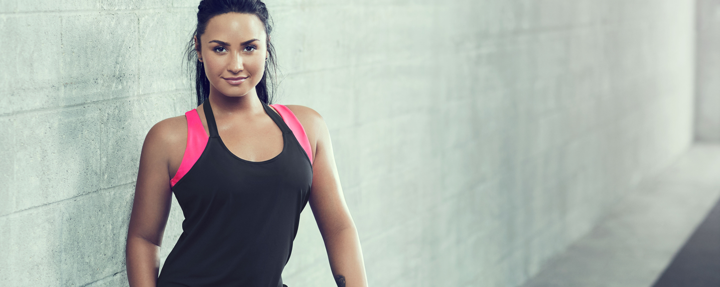Demi Lovato wearing a black sports bra and black leggings.