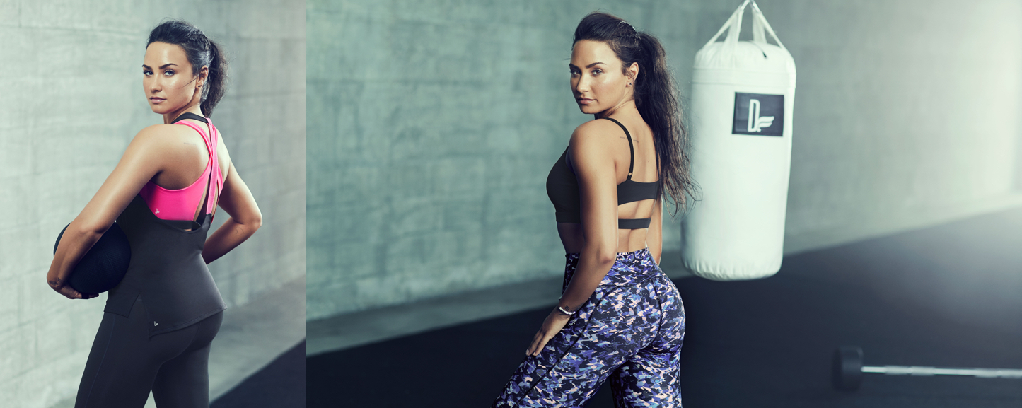 Demi Lovato wearing a black and pink sports bra and leggings.