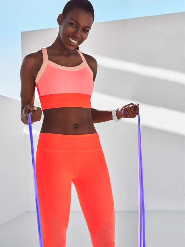 Woman wearing leggings and a sports bra in a hot orange colour