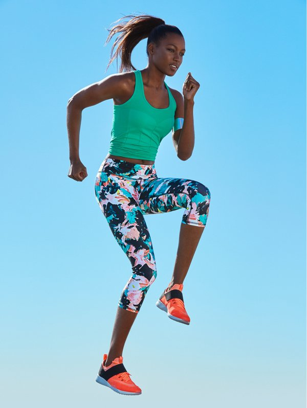 Woman sprinting in printed leggings and a vest top