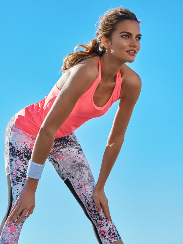 Woman wearing printed leggings and a pink vest top