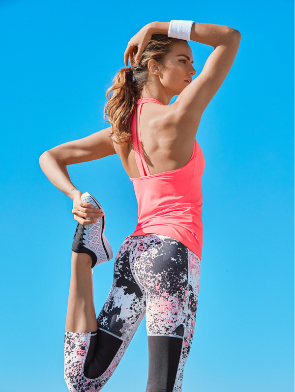 Woman stretching in printed leggings and a pink vest top