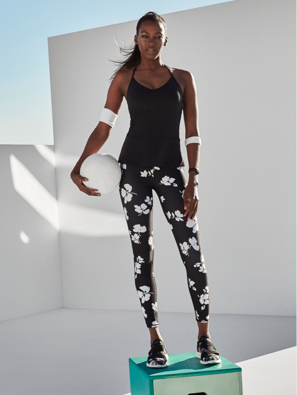 Woman wearing a floral printed legging and black vest top