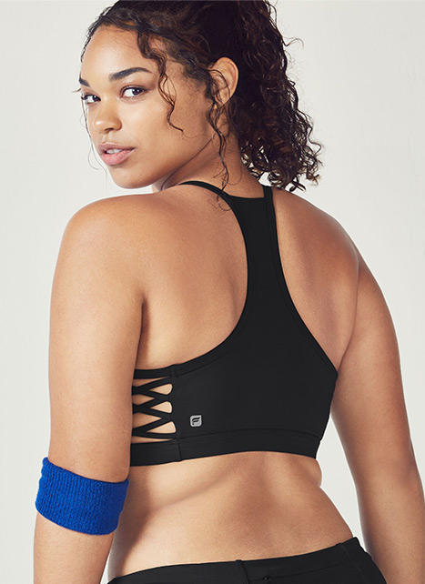 Plus size model wearing a black sports bra.