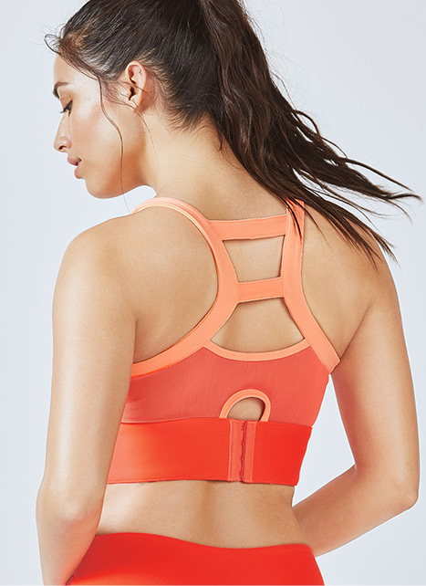 Model wearing orange high impact bra.