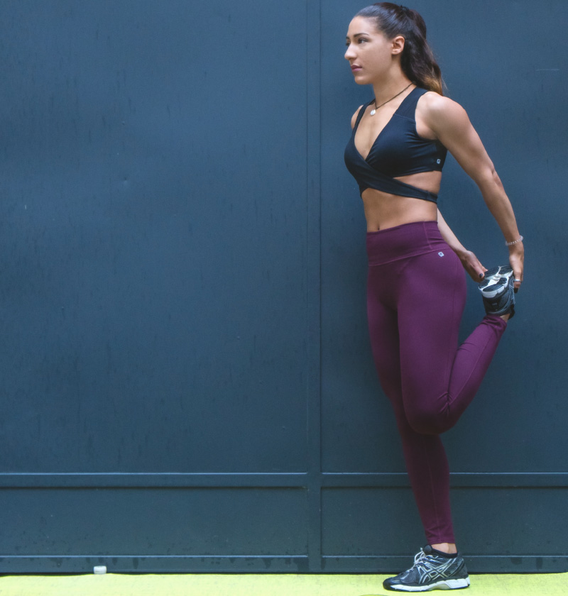 A woman stretching in violet leggings and a black sports bra.