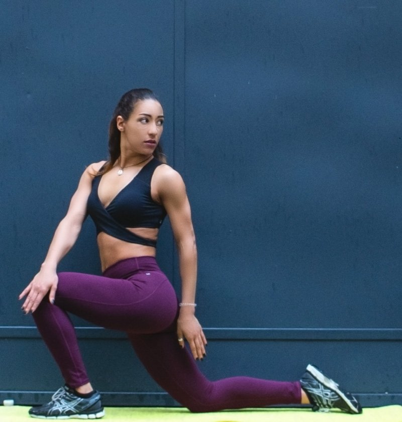 A woman kneeling in violet leggings and a black sports bra.