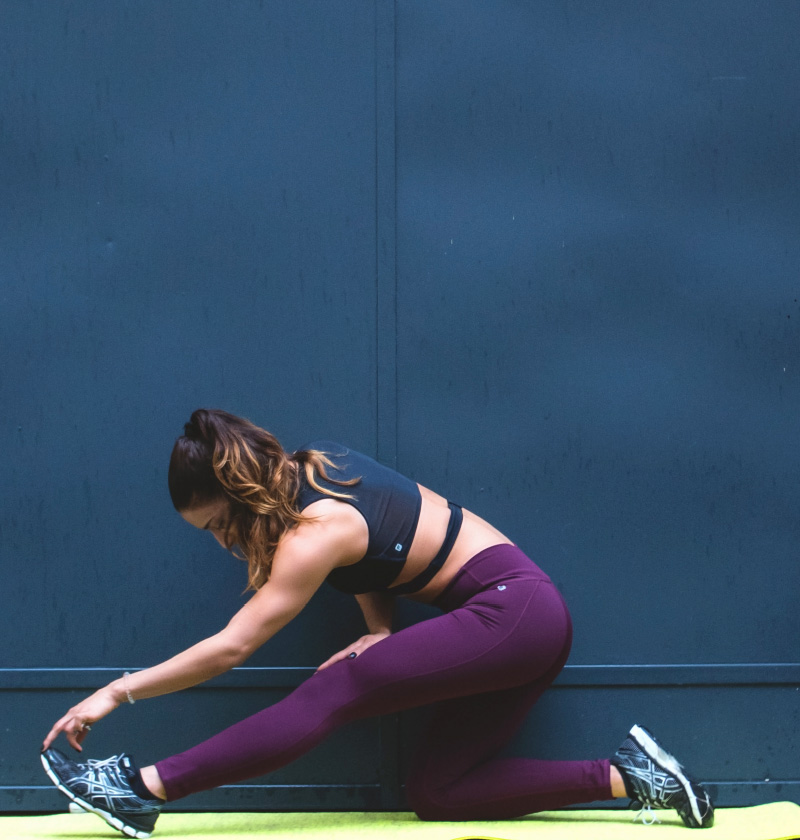 A woman stretching in workout gear.