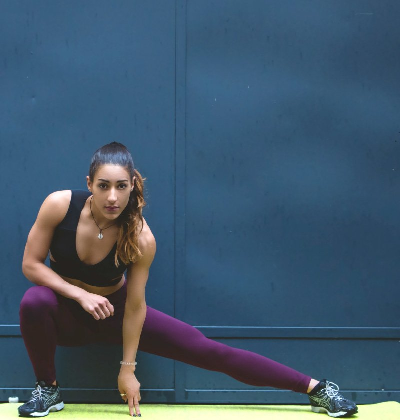 A woman stretching in running gear.