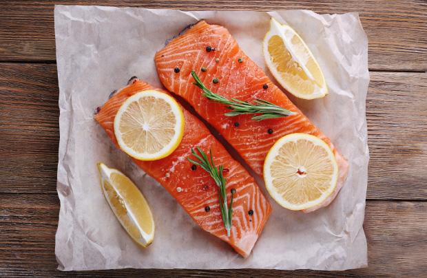 Two pieces of salmon with lemon wedges.