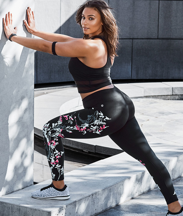 Plus size model wearing Fabletics and stretching outside