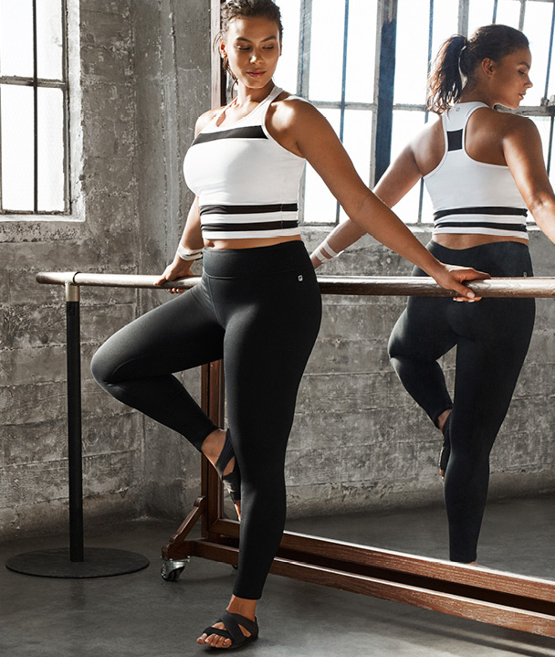 Plus size model wearing Fabletics at ballet barre